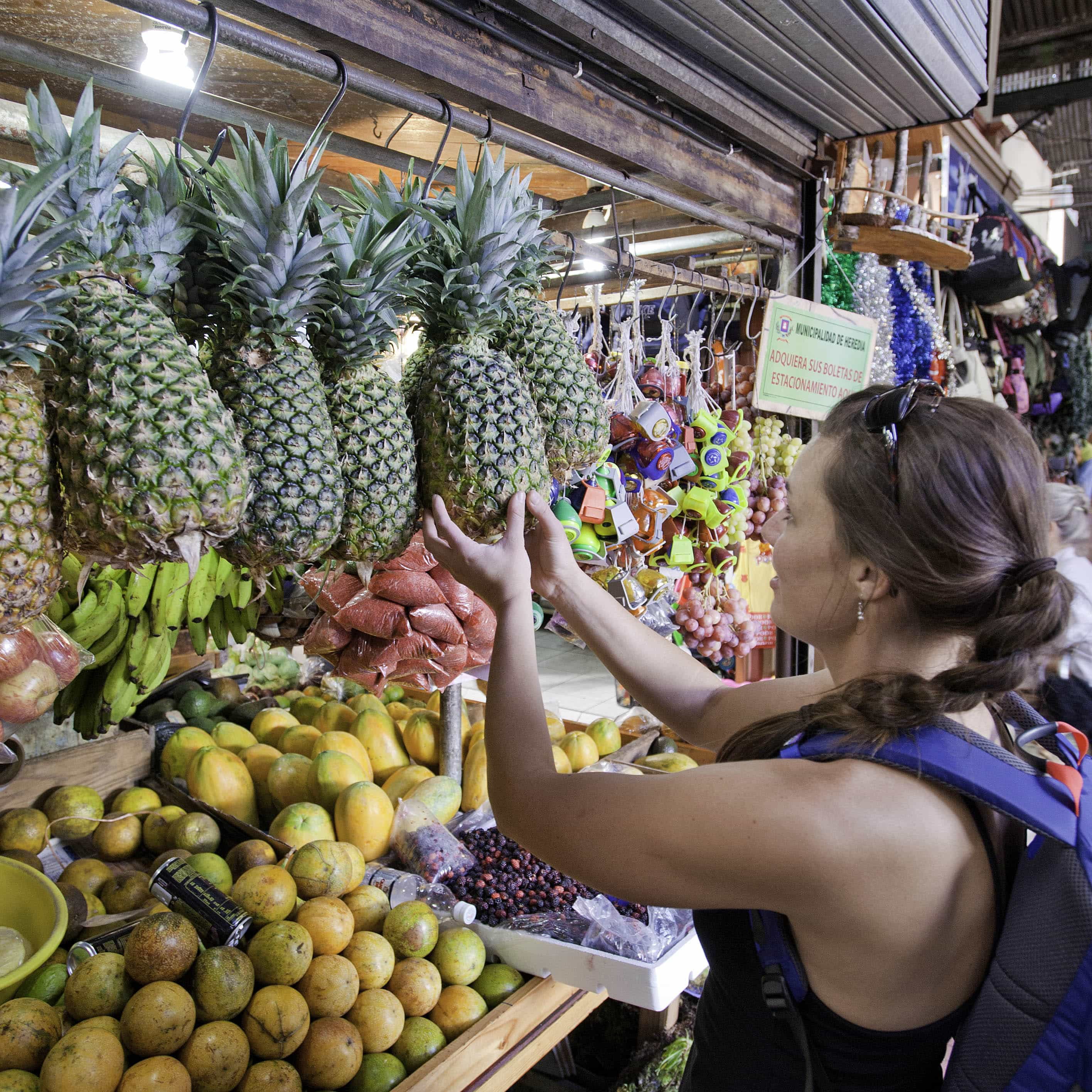 Woman selecting pineapple at a market