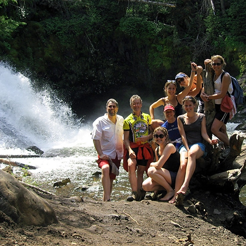 Group standing by waterfall